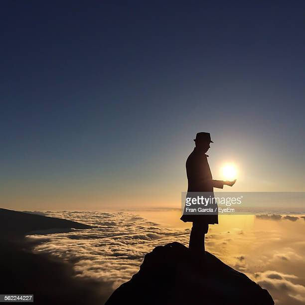 Optical Illusion Of Silhouette Man Holding Sun At Mountain Peak Against Clear Blue Sky