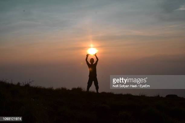 Optical Illusion Of Silhouette Man Holding Sun While Standing On Field Against Sky During Sunset