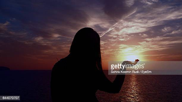 Optical Illusion Of Silhouette Woman Holding Sun During Sunset