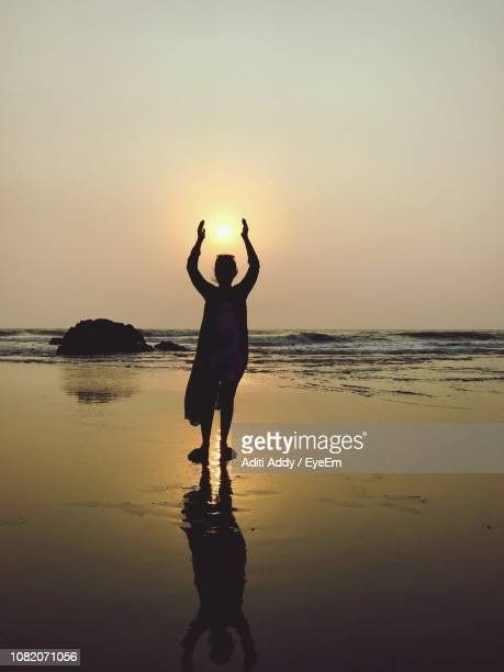 Optical Illusion Of Silhouette Woman Holding Sun While Standing At Beach