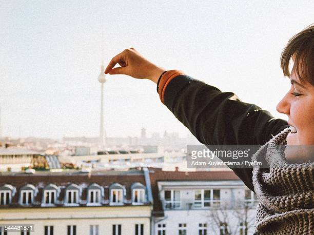 Optical Illusion Of Smiling Woman Touching Fernsehturm Tower Against Clear Sky