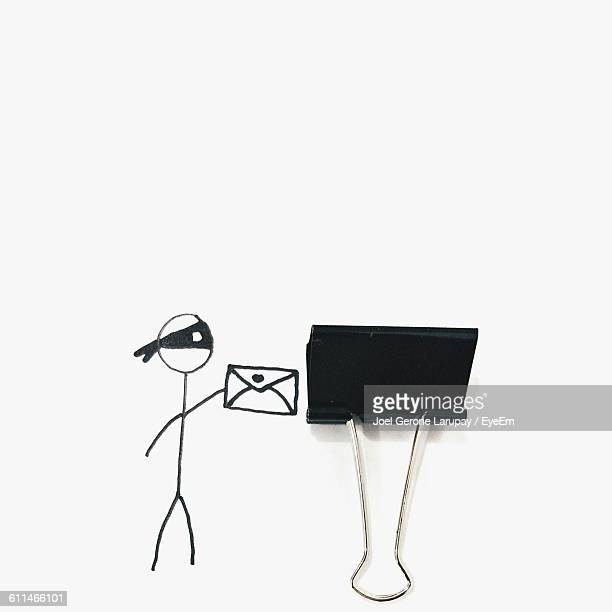 Optical Illusion Of Stick Figure With Paper Clip Over White Paper