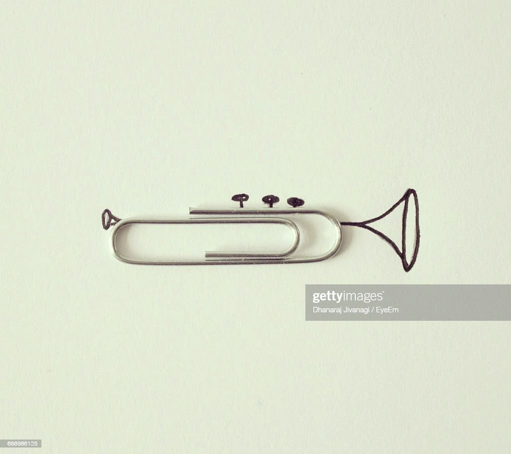 Optical Illusion Of Trumpet Made From Paper Clip On White Background : Stock Photo