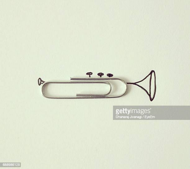 optical illusion of trumpet made from paper clip on white background - paper clips stock photos and pictures