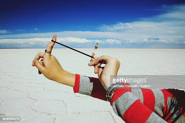 Optical Illusion Of Woman Aiming Slingshot With Man At Salar De Uyuni
