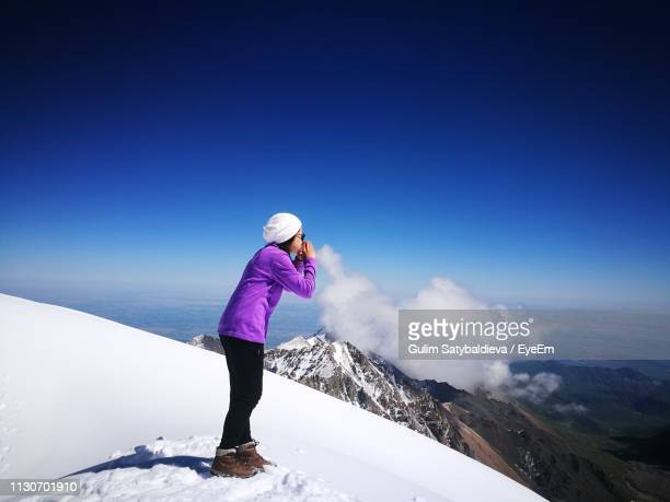optical illusion of woman blowing cloud against sky - kyrgyzstan stock pictures, royalty-free photos & images