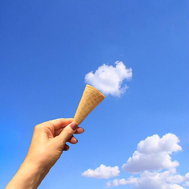 Optical Illusion Of Woman Hand Holding Ice Cream Cone Towards Clouds Wall Art