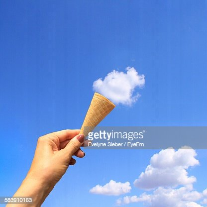 Optical Illusion Of Woman Hand Holding Ice Cream Cone Towards Clouds