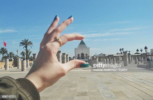optical illusion of woman holding hassan tower against blue sky - rabat morocco stock pictures, royalty-free photos & images