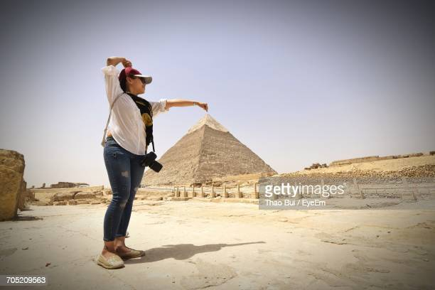 Optical Illusion Of Woman Holding Pyramid Against Clear Sky