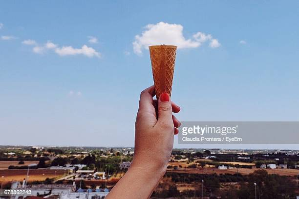 Optical Illusion Of Woman Holing Clouds On Ice Cream Cone