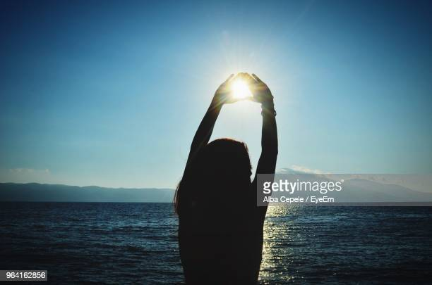 Optical Illusion Of Woman Making Heart Shape At Beach Against Sky During Sunset