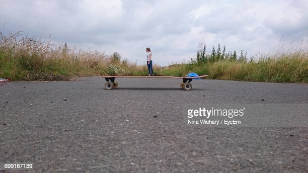 optical illusion of woman standing on skateboard against cloudy sky - optical illusion stock photos and pictures