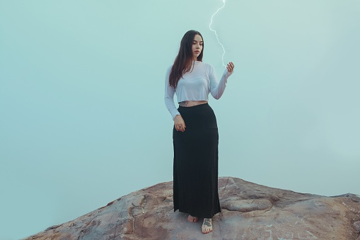Optical Illusion Of Young Woman Holding Lightning Against Clear Sky - gettyimageskorea