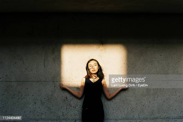 optical illusion of young woman holding window shadow falling on wall - licht stock-fotos und bilder