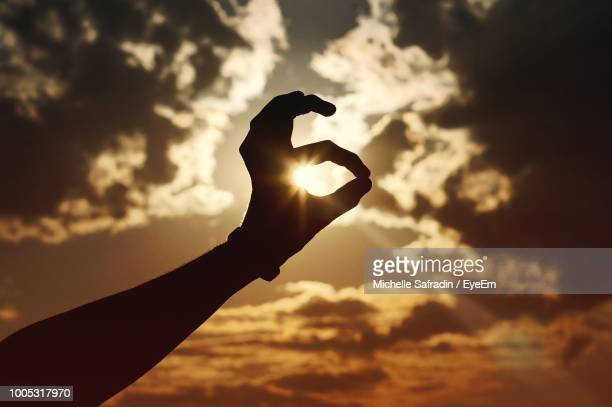 Optical Illusion On Silhouette Hand Holding Sun Against Cloudy Sky During Sunset