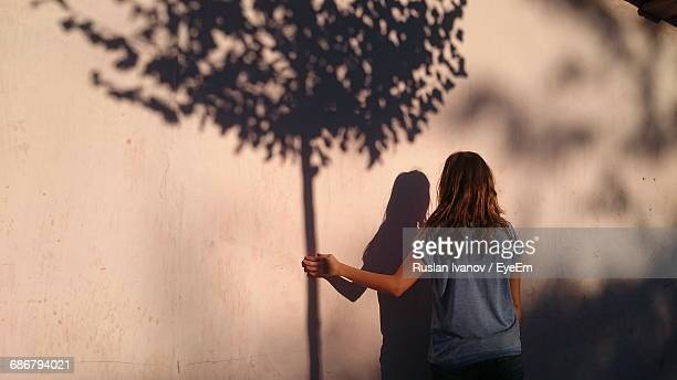 optical illusion on woman holding tree shadow on wall - optical illusion stock photos and pictures
