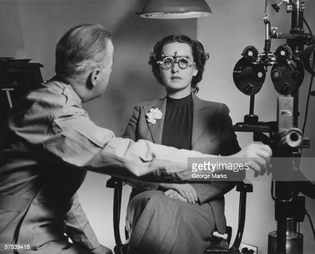 Optician examining patient's eyes, (B&W)