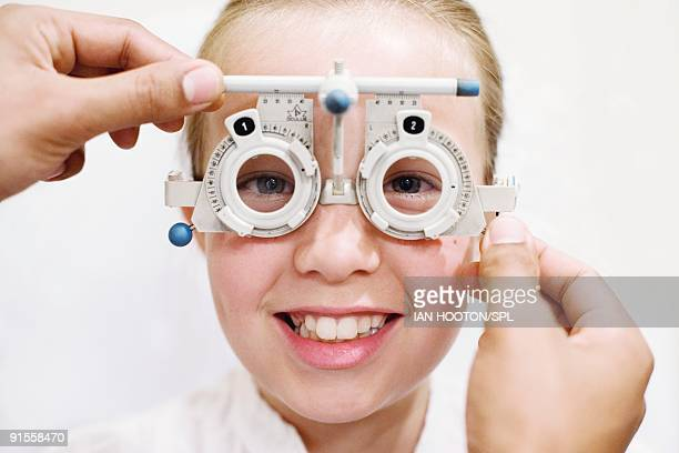 Optician helping girl (10-11) to choose pair of glasses