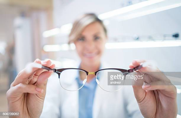 optician holding glasses - myopia stock photos and pictures