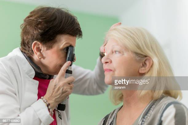 Optician looking into patients eyes
