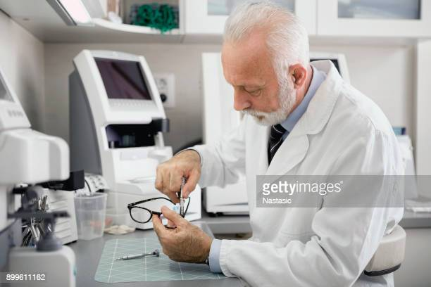 optician repairing eye glasses in workshop with professional tools - lens optical instrument stock pictures, royalty-free photos & images