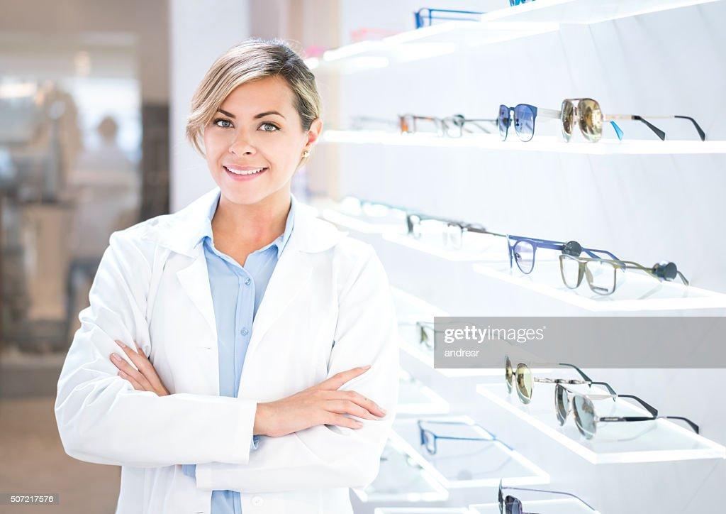 Optician selling glasses at the optics : Stock Photo