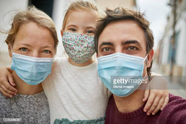 optimistic family selfie during coronavirus emergency. all wearing protective face mask - family stock pictures, royalty-free photos & images