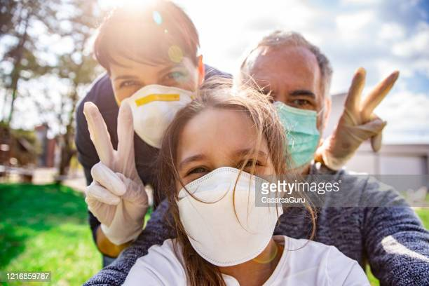 optimistic family selfie during coronavirus emergency - protective face mask stock pictures, royalty-free photos & images