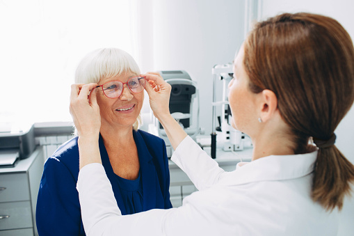 Optomerist is putting new glasses on matue woman face 1055656458
