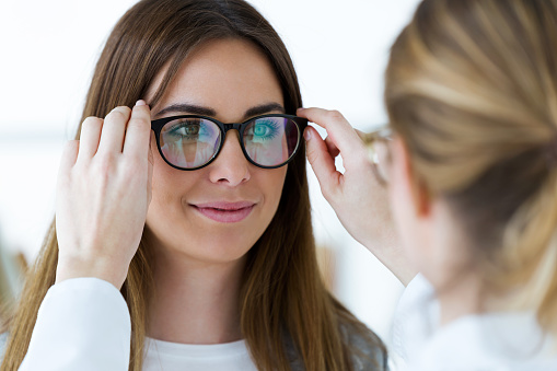 Optometrist and pretty young woman choosing eyeglasses in optics. 953624090