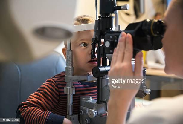 Optometrist checking boy's eyes at clinic
