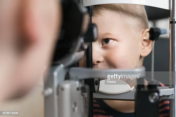 Optometrist checking boy's eyesight at clinic
