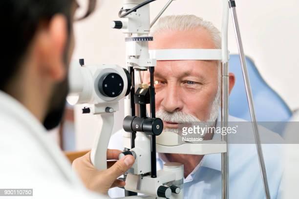 Optometrist checking senior man with optometry machine