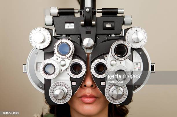 optometrist diopter with female - lens optical instrument stock pictures, royalty-free photos & images