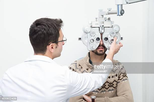 Optometrist examining eyesight of a man