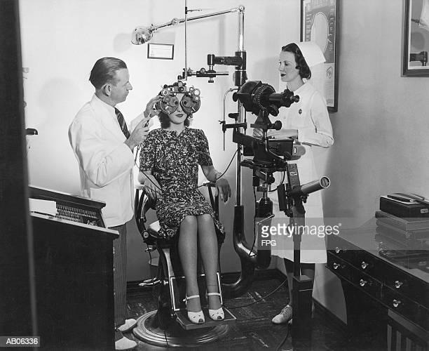 optometrist examining woman's eyes (b&w) - siglo xx fotografías e imágenes de stock