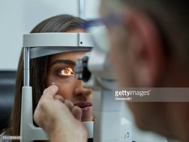 optometrist examining young woman's eye, contact lens on index finger - contact lens stock pictures, royalty-free photos & images