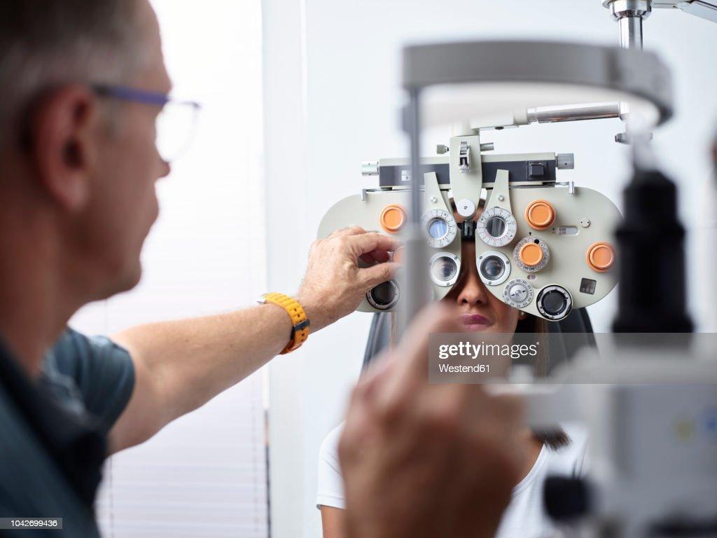 Optometrist examining young woman's eye : Stock Photo
