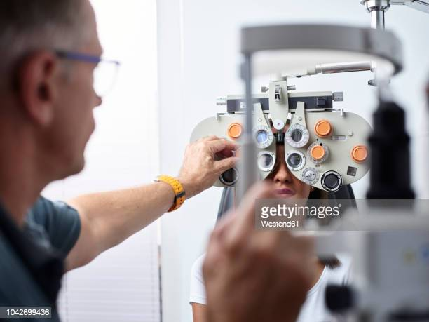 optometrist examining young woman's eye - optometry stock pictures, royalty-free photos & images