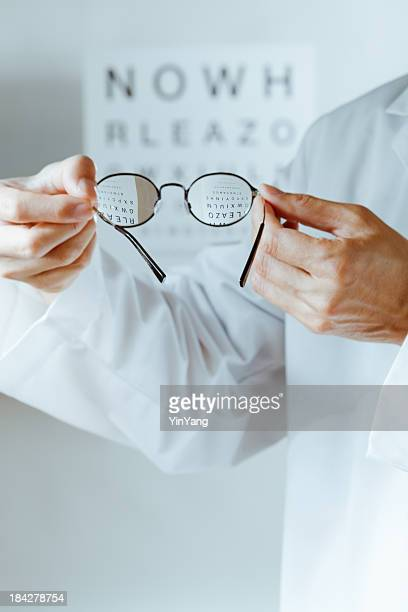 optometrist holding eyeglasses lens over eye chart for medical examination - lens optical instrument stock pictures, royalty-free photos & images