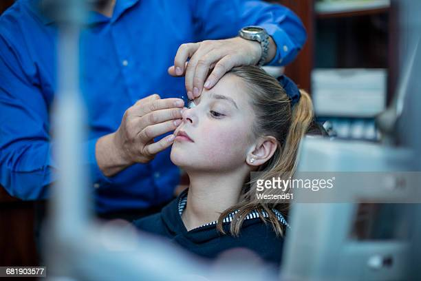 Optometrist inserting contact lens into girls eye