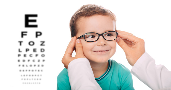 Optometrist is putting new glasses on Little boy face 1055656456