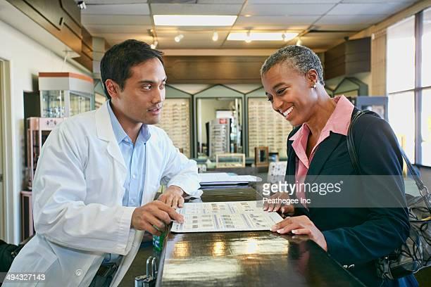 Optometrist talking to patient in office
