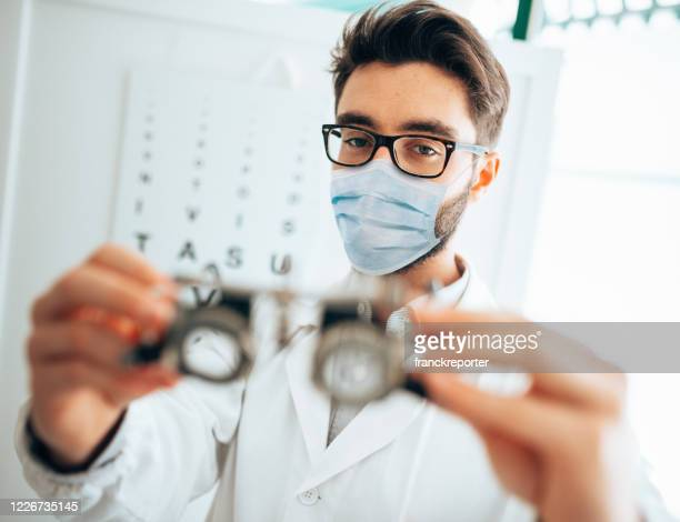 optometrist testing glass during the covid19 - eye test stock pictures, royalty-free photos & images