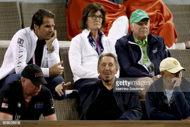 Oracle Cofounder Larry Ellison speaks to tournament director Tommy Hass while Maria Sharapova plays Naomi Osaka during the BNP Paribas Open at the...