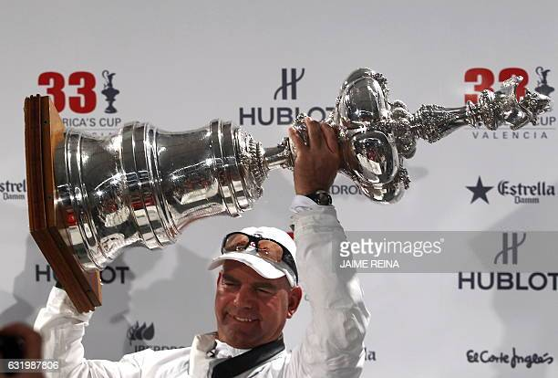 Oracle's tactician John Kostecki holds the trophy during a press conference after winning the 33rd America's Cup on February 14 2010 in Valencia US...