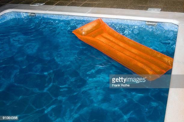 orange air mattress on top of blue water in pool