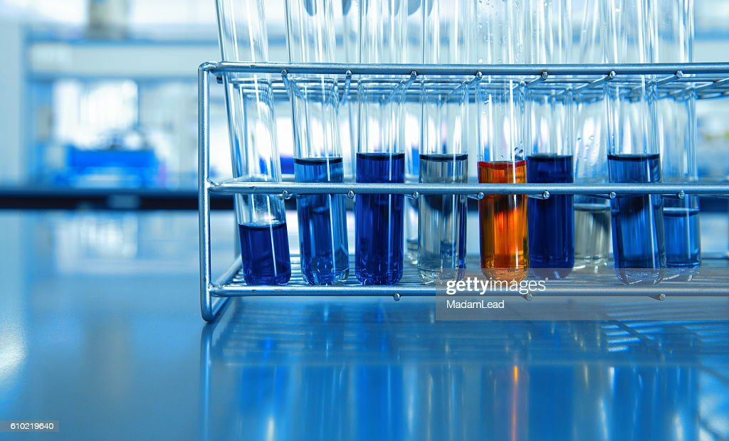 orange and blue chemical solution in test tubes in science lab : Foto de stock
