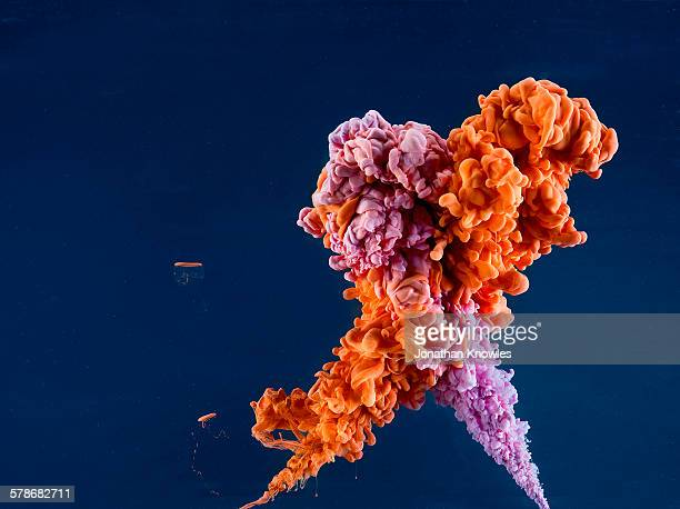 Orange and purple paint in water, dark background